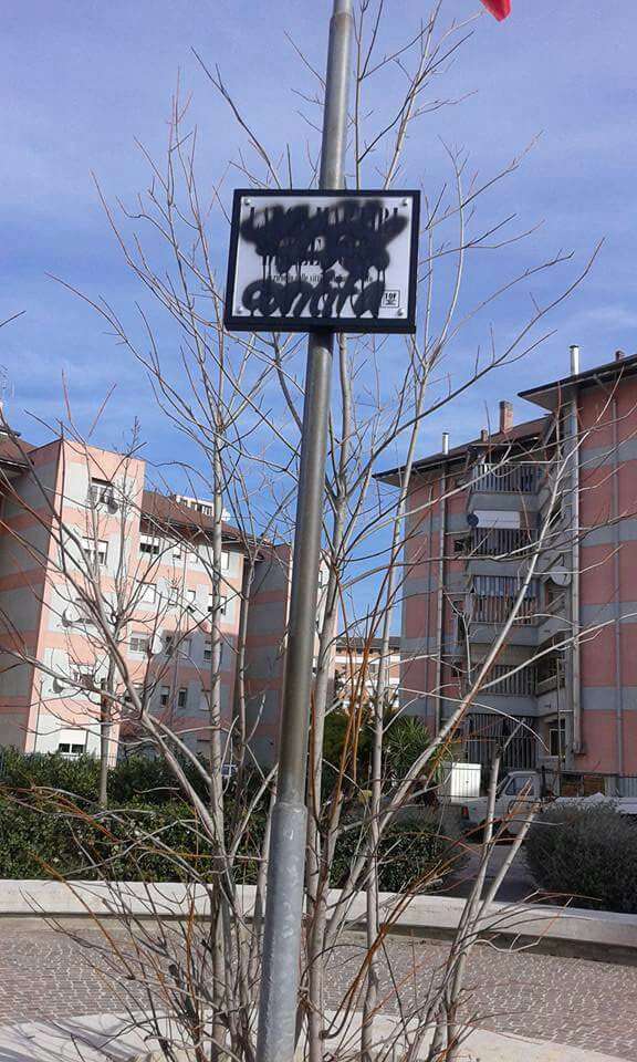 targa imbrattata con scritta Largo Martiri delle Foibe